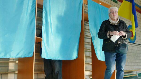 Жители Киева во время голосования на одном из избирательных участков города в день второго тура выборов президента Украины