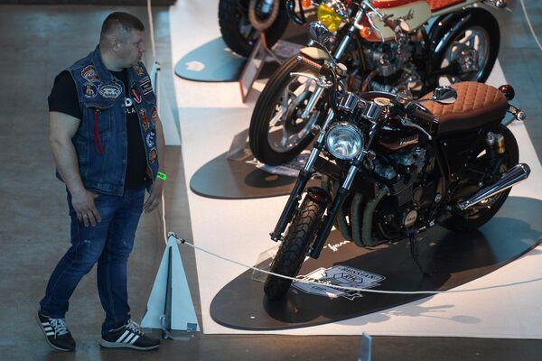Посетитель рассматривает мотоцикл марки Yamaha на Международном мотосалоне IMIS в Санкт-Петербурге