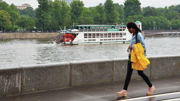 Девушка идет по Фрунзенской набережной в Москве