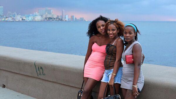 Молодые кубинки отдыхают на набережной Малекон в Гаване