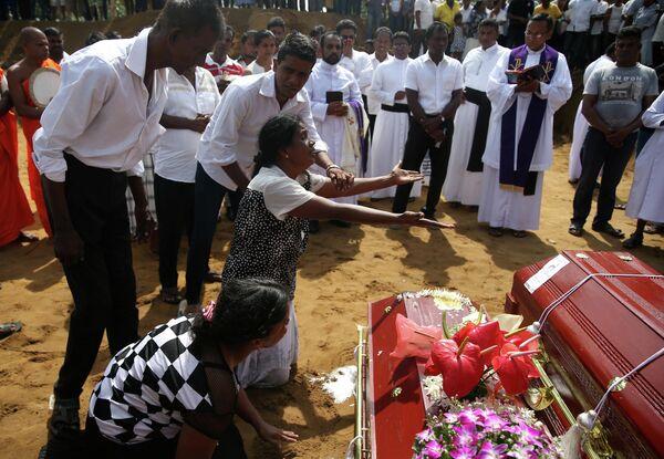 Женщина у могилы родственника, погибшего во время взрывов в пасхальное воскресенье в Негомбо, Шри-Ланка. 23 апреля 2019