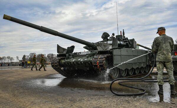 Военнослужащий моет танк Т-72, который примет участие в параде Победы на Красной площади 9 мая