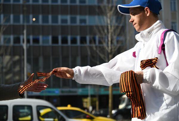 Волонтер раздаёт георгиевские ленточки на Зубовском бульваре в Москве в рамках ежегодной акции Георгиевская ленточка