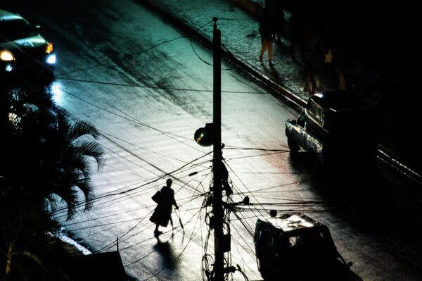 Женщина идет по улице после ливня в городе Порт-о-Пренс на Гаити