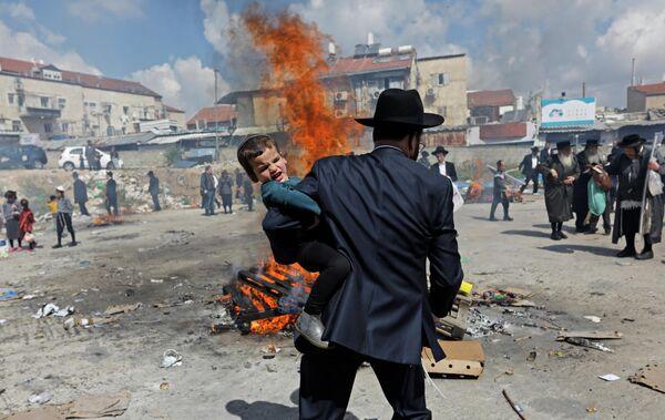Ультраортодоксальный еврей держит ребенка во время ритуала Biur Chametz накануне Пасхи