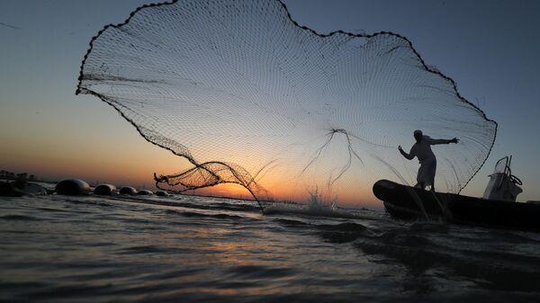 Рыбак закидывает сеть неподалеку от Абу-Даби, ОАЭ