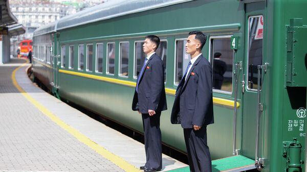 Сотрудники службы безопасности у вагона бронепоезда лидера КНДР Ким Чен Ына на железнодорожном вокзале Владивостока
