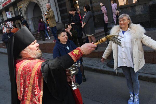 Священник освящает людей во время пасхального крестного хода во Владивостоке