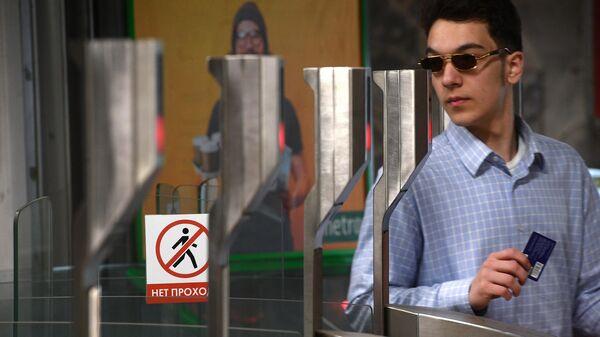 Пассажир московского метро проходит через турникет на станции Октябрьское Поле