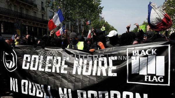 Протестующие в масках на традиционной рабочей первомайской демонстрации в Париже, Франция. 1 мая 2019