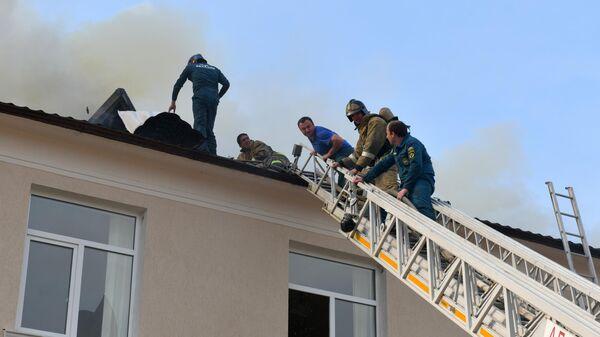 Сотрудники пожарной службы на крыше здания русской средней школы №2 имени А.С. Пушкина в Сухуме, где произошло возгорание. 2 мая 2019