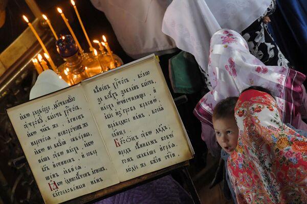 Религиозная книга и прихожане в одном из храмов духовного центра старообрядчества Рогожская слобода в Москве