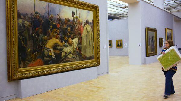 Сотрудница музея возле картины Запорожцы пишут письмо турецкому султану во время подготовки выставки Ильи Репина в Третьяковской галерее на Крымском валу