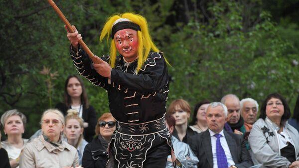 Актёр в сцене из спектакля Пионовая беседка, который проходит в рамках Международного театрального фестиваля имени А.П. Чехова в Аптекарском огороде в Москве