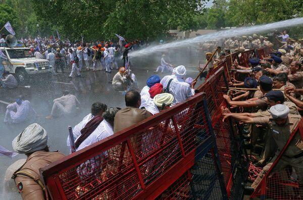 Полиция поливает водой демонстрантов во время акции протеста в индийском Чандигархе