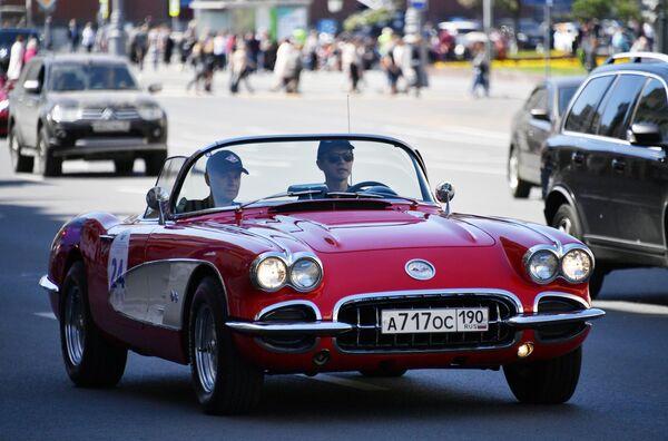 Участники в автомобиле Chevrolet 1962 Corvette GM принимают участие в ралли классических ретро-автомобилей в Москве
