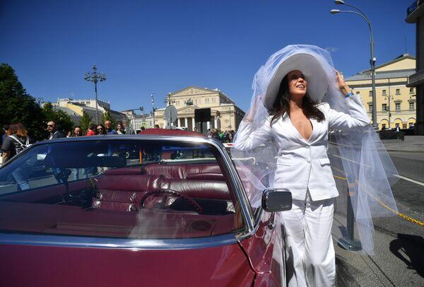 Девушка у автомобиля Cadillac Eldorado 1978 года выпуска, который принимает участие в ралли классических ретро-автомобилей в Москве
