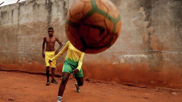 Семнадцатилетний Gaelle Dule Asheri играет в футбол с друзьями в Яунде, Камерун