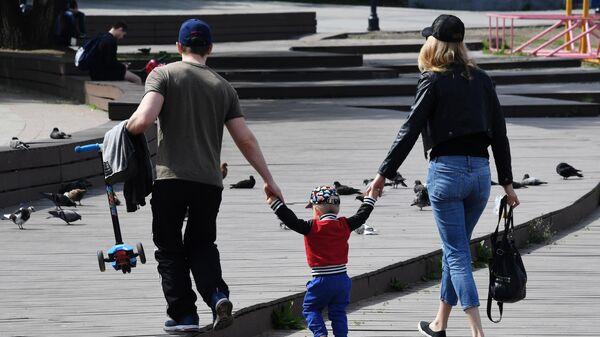 Семейная пара с ребенком гуляют по набережной