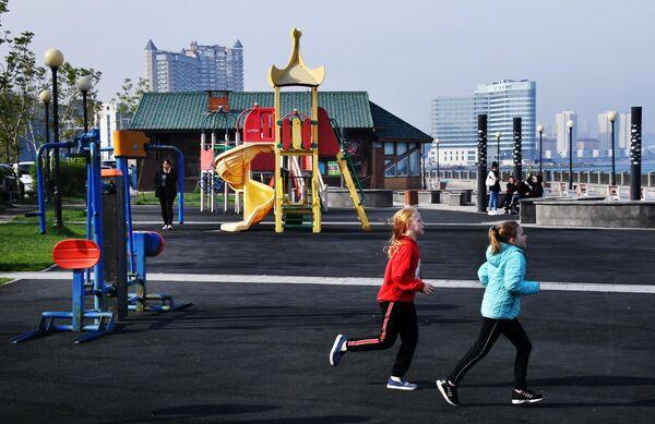 Дети бегают по детской площадке на набережной Спортивной гавани во Владивостоке