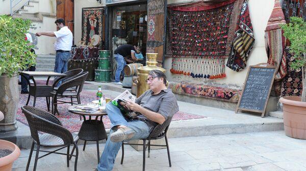 Житель Баку читает газету в уличном кафе в Старом городе