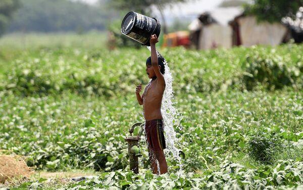 Мальчик поливает себя водой во время жары в Нью-Дели