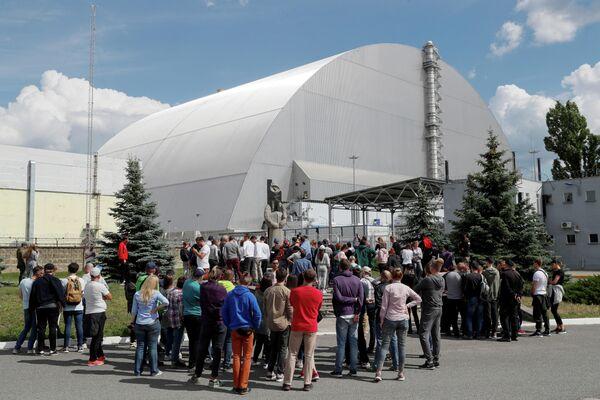Туристы возле Нового безопасного конфайнмента над старым саркофагом, покрывающим поврежденный четвертый реактор на Чернобыльской АЭС