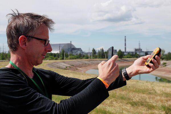 Турист фотографирует дозиметр возле Нового безопасного конфайнмента над старым саркофагом, покрывающим поврежденный четвертый реактор на Чернобыльской АЭС