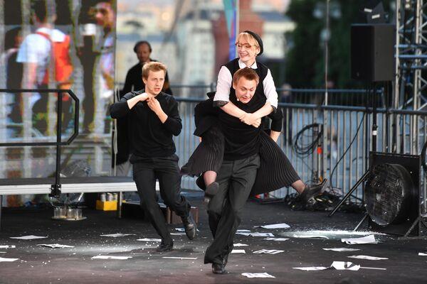 Актеры театра Школа современной пьесы в сцене из спектакля Шинель/Пальто на ежегодном российском книжном фестивале на Красной площади