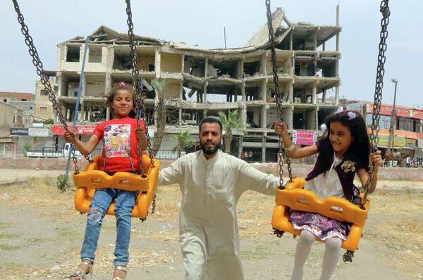 Девочки катаются на качелях возле поврежденного здания в первый день мусульманского праздника Ид аль-Фитр в городе Ракка, Сирия