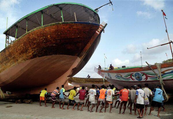 Рыбаки спускают лодку на берег Аравийского моря недалеко от Мумбаи, Индия