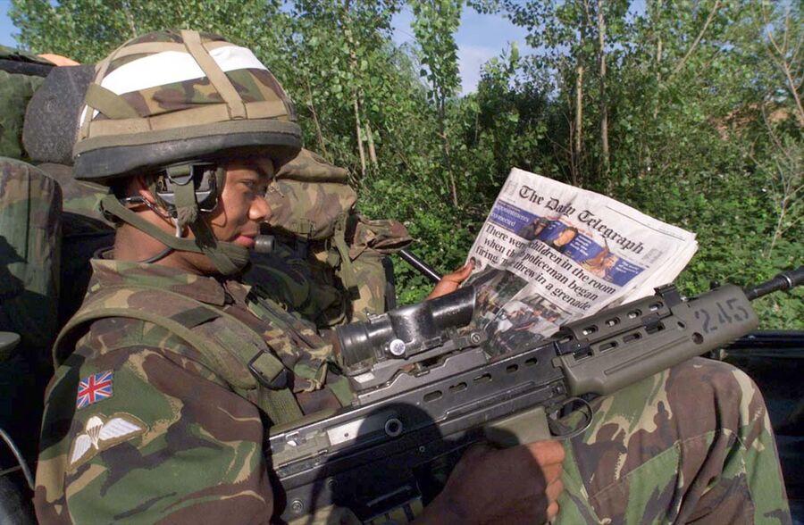 Британский солдат-гуркх читает газету на КПП НАТО в Приштине