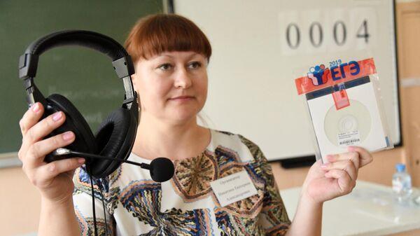 Учитель демонстрирует конверт с диском, в котором содержатся задания для ЕГЭ по английскому языку