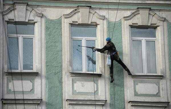 Промышленный альпинист моет окна здания на улице Воздвиженка в Москве