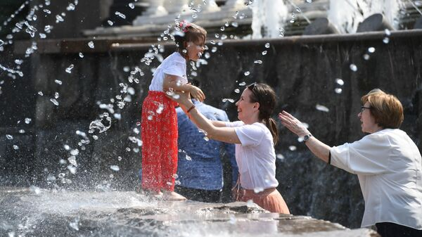 Жители города отдыхают у фонтанов на Манежной площади в Москве
