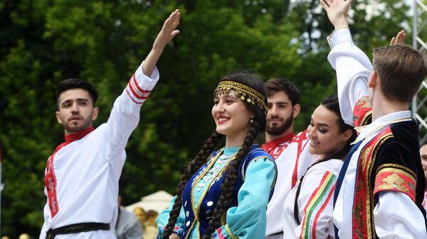 Молодые люди в национальных костюмах выступают на Дне России в парке им. М. Горького в Казани