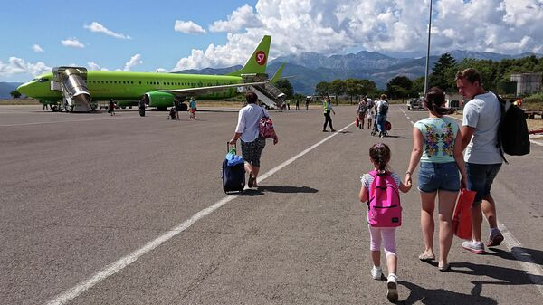Туристы осуществляют посадку в самолет
