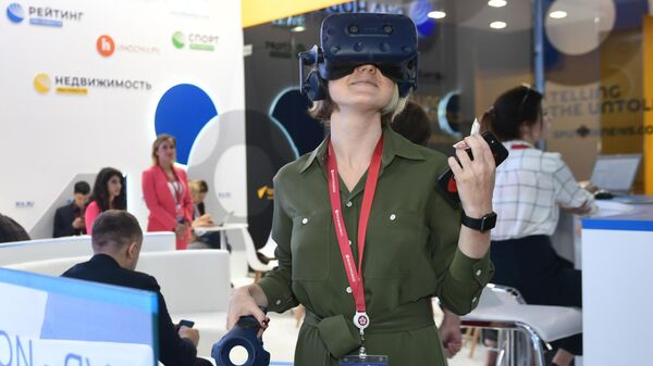 Посетительница в очках виртуальной реальности на стенде МИА Россия сегодня