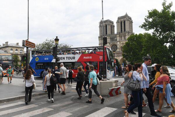 Горожане и туристы на площади у Собора Парижской Богоматери (Notre Dame de Paris) в Париже