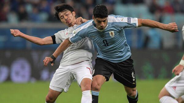 Полузащитник сборной Японии Гаку Сибасаки (слева) и нападающий сборной Уругвая Луис Суарес