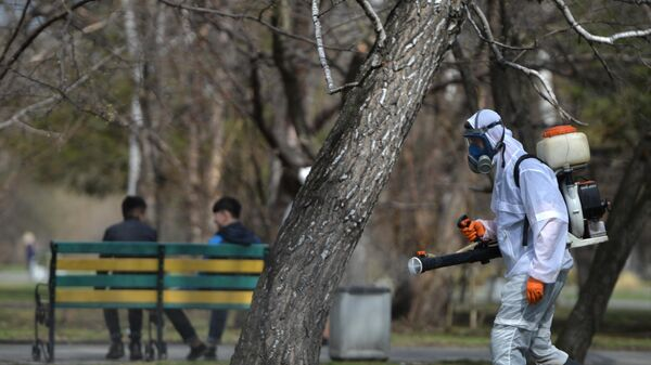 Сотрудник службы дезинфекции проводит акарицидную обработку против клещей в парке