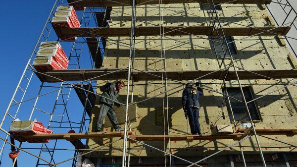 Рабочие утепляют фасад строящегося жилого дома