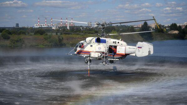 Пожарно-спасательный вертолет Ка-32А осуществляет забор воды на показательном тушении пожара  в Москве