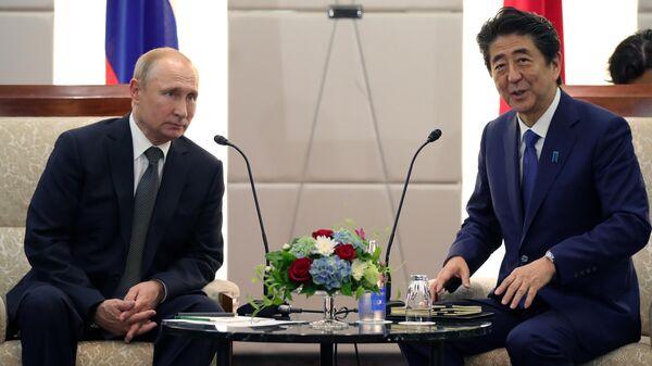 Президент РФ Владимир Путин и премьер-министр Японии Синдзо Абэ во время встречи в Осаке