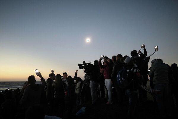 Люди наблюдают солнечное затмение в Ла Серена, Чили