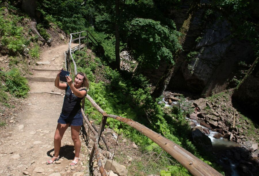Девушка делает селфи в природном парке водопадов Менделиха на горнолыжном курорте Роза Хутор в Сочи