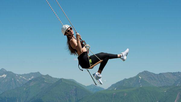 Девушка катается на тарзанке на горнолыжном курорте Роза Хутор в Сочи