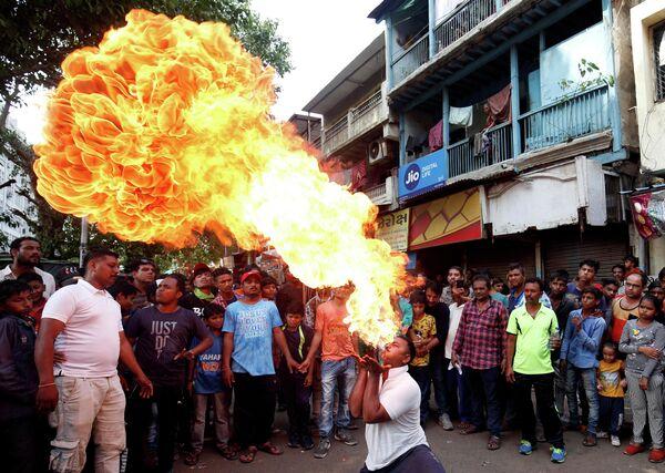 Индуист выполняет трюк с огнем во время репетиции праздника Ратха-ятра. Ахмадабад, Индия
