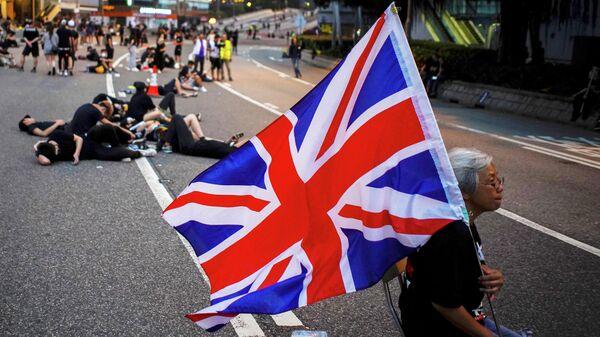 Женщина держит флаг Великобритании во время акции за отмену закона об экстрадиции в Гонконге