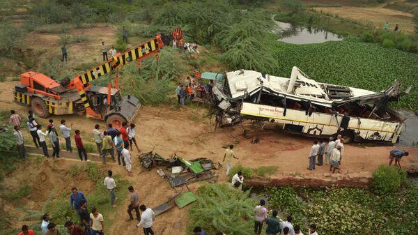 Кран эвакуирует поврежденный автобус после того, как он упал с моста  в канал на окраине Агры, Индия. 8 июля 2019